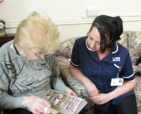 Moorcare Assistant sits beside a Moorcare user who is showing her a collection of old photographs.